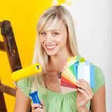 Woman with Paint roller brush and cards. Smiling woman holding a paint roller brush and paint shade card Royalty Free Stock Photography