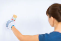Woman with paintbrush colouring the wall Stock Photo