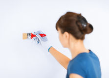 Woman with paintbrush colouring the wall Royalty Free Stock Photography