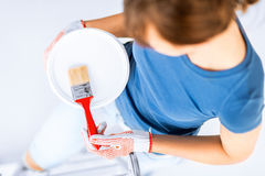 Woman with paintbrush and paint pot Stock Photos