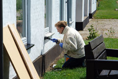 Woman with a paintbrush painting a house royalty free stock photography