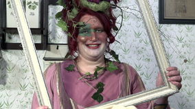 Woman with painted face and a plant on her head holds a picture frame stock video footage