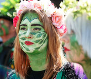 Woman in painted green with flower hat Royalty Free Stock Photo