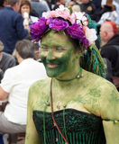 Woman in painted green with garlands hat Stock Images