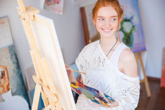 Woman painter holding palette with oil paints in art studio. Happy lovely cute young woman painter holding palette with oil paints and painting on canvas in art Royalty Free Stock Photos