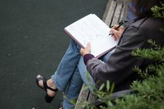 a woman painter outdoors doing sketches with a pen on paper, plein air stock images