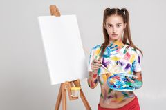 Woman painter soiled in colorful paint draws on canvas. Stock Image
