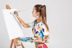 Woman painter soiled in colorful paint draws on canvas. Stock Photography