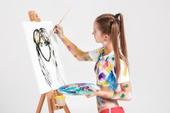 Woman painter soiled in colorful paint draws on canvas. Royalty Free Stock Images