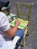 Woman painting. Wooden chair decorated Royalty Free Stock Images