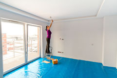 Woman painting apartment ceiling Stock Photography