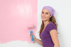 Woman painting baby nursery pink. With roller brush Stock Images