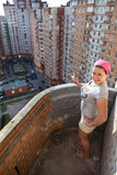 Woman painting balcony apartment on a high floor Stock Images