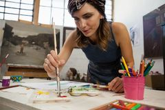 Woman painting on book in drawing class royalty free stock photos