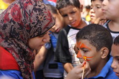 A woman painting a boys face at charity event. A woman holding a brush painting a boys face at a charity event for children, to help children, sonaa el hayah Stock Photography