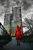 Woman painting buildings. Woman in red coat painting buildings in positive colors at dramatic thunder sky background royalty free stock image