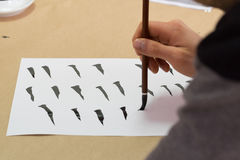 Woman painting calligraphy. Woman holding wooden paint brush performing calligraphy exercises during workshop stock photo