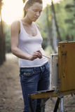 Woman Painting On Canvas In Forest Clearing. Young woman painting on canvas in forest clearing royalty free stock photos