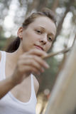Woman Painting On Canvas In Park. Closeup of beautiful young woman painting on canvas in park stock photo