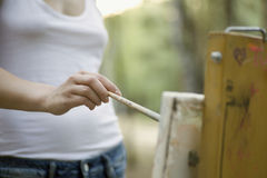 Woman Painting On Canvas In Park. Midsection of young woman painting on canvas in park royalty free stock photo
