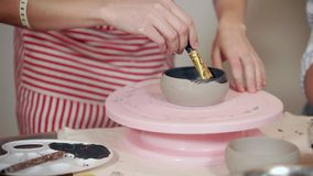Woman is painting a ceramic cup in pottery, rotating stand, close-up. Female artist is coloring by black dye clay bowl in ceramic workshop. She is using brush stock video