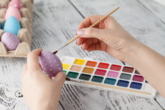 Woman painting Easter eggs, on white wooden background Stock Photography