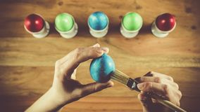 Woman painting easter eggs. On a brown wooden table with some already painted eggs standing in the background Stock Photography