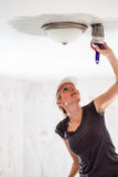 Woman Painting the Edges of the Ceiling Stock Photo