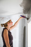Woman Painting the Edges of the Ceiling Stock Images