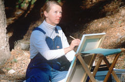Woman painting en pleine air. Female artist painting on canvas in the woods in Santa Fe, New Mexico Royalty Free Stock Photos