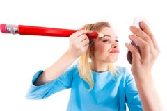 Woman painting eyebrows using regular pencil. Funny silly woman trying to paint her eyebrows using big huge oversized regular student pencil. Make up fun concept Royalty Free Stock Photos