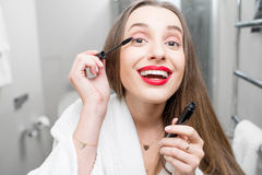 Woman painting eyelashes Royalty Free Stock Photos
