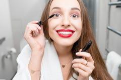 Woman painting eyelashes Stock Images