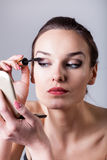 Woman painting eyelashes using mascara Royalty Free Stock Image