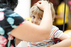 Woman painting face of kid indoors Stock Images