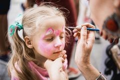 Woman painting face of kid outdoors Royalty Free Stock Photo