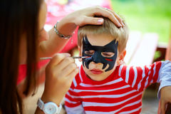 Woman painting face of kid outdoors Stock Images