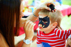 Woman painting face of kid outdoors Stock Image