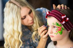 Woman painting the face of a little girl stock photography