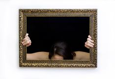 Woman in a painting frame. Young woman in a painting frame - hiding Royalty Free Stock Photo