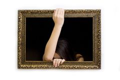 Woman in a painting frame. Young woman in a painting frame on a wall peeking out Royalty Free Stock Images