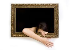 Woman in a painting frame. Young woman in a painting frame on a wall tries to exit, one hand is out and touching the wall. She is peeking out Stock Photography