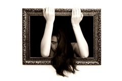 Woman in a painting frame. Young woman in a painting frame on a wall tries to exit, she looks angry for being caught beyond Royalty Free Stock Images