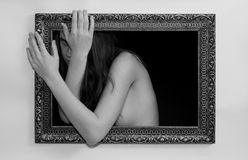 Woman in a painting frame. Young woman in a painting frame on a wall tries to exit, she seems scared to leave her world Royalty Free Stock Photography