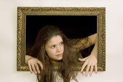Woman in a painting frame. Young woman in a painting frame on a wall tries to exit, she seems curios of the world beyond the canvas Royalty Free Stock Image