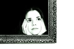 Woman in a painting frame. Young woman in a painting frame on a wall . She seems curios of the world beyond the canvas Royalty Free Stock Photo