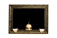 Woman in a painting frame. Young woman in a painting frame on a wall. She is peeking out Stock Image