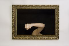 Woman in a painting frame. Young woman in a painting frame on a wall, showing her fist Stock Images
