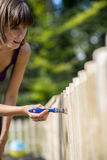 Woman painting a garden fence royalty free stock photo