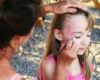 Woman painting girls face. Woman painting young girls face outdoors Stock Photo